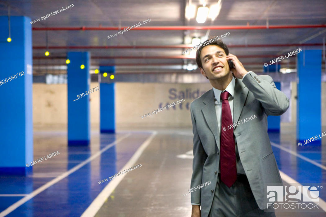 Stock Photo: Businessman with mobile phone. Parking lot.