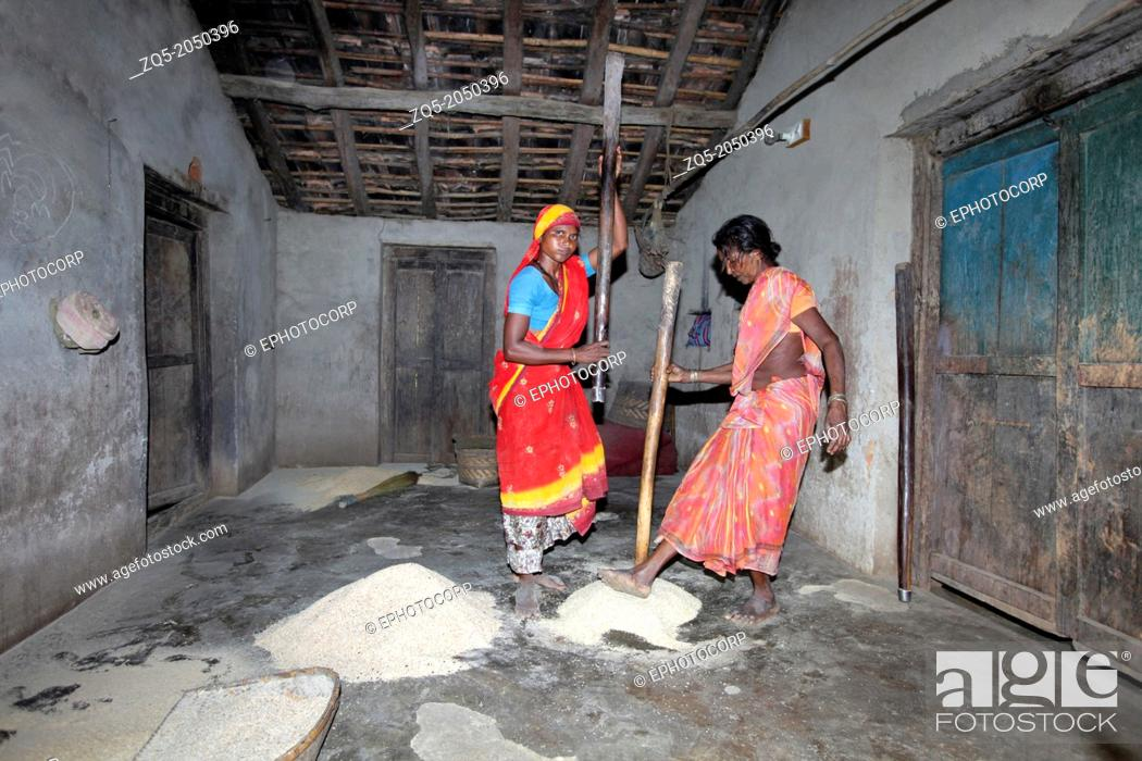 Stock Photo: Tribal woman husking grains in the house, Madia tribe, Bhamragad, Maharashtra, India. Madia are one of the endogamous Gond tribes living in Chandrapur District.