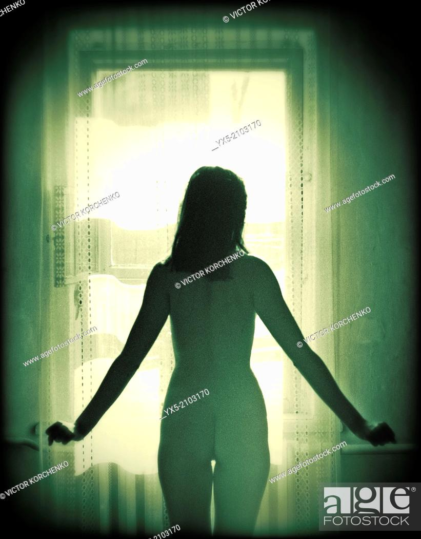 Imagen: Nude young woman standing at a window.