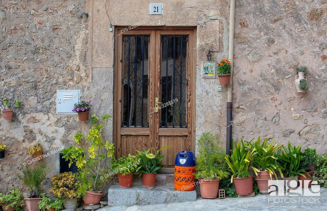 Imagen: VALLDEMOSSA, MALLORCA, SPAIN - MARCH 21, 2019: Flowers and butane gas bottle outside door in the old town on March 21, 2019 in Valldemossa, Mallorca, Spain.