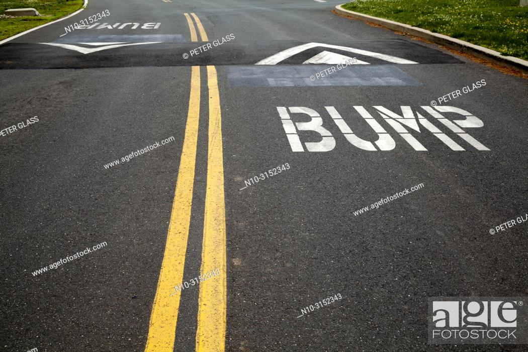 "Stock Photo: Street with double yellow lines, speed bumps, and the word """"Bump"""" painted on it."