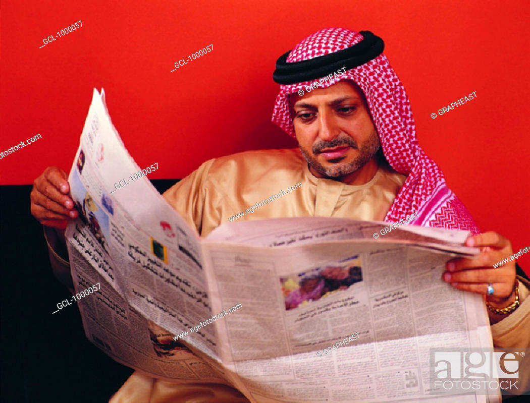 Stock Photo: Arab man reading Arabic newspaper.