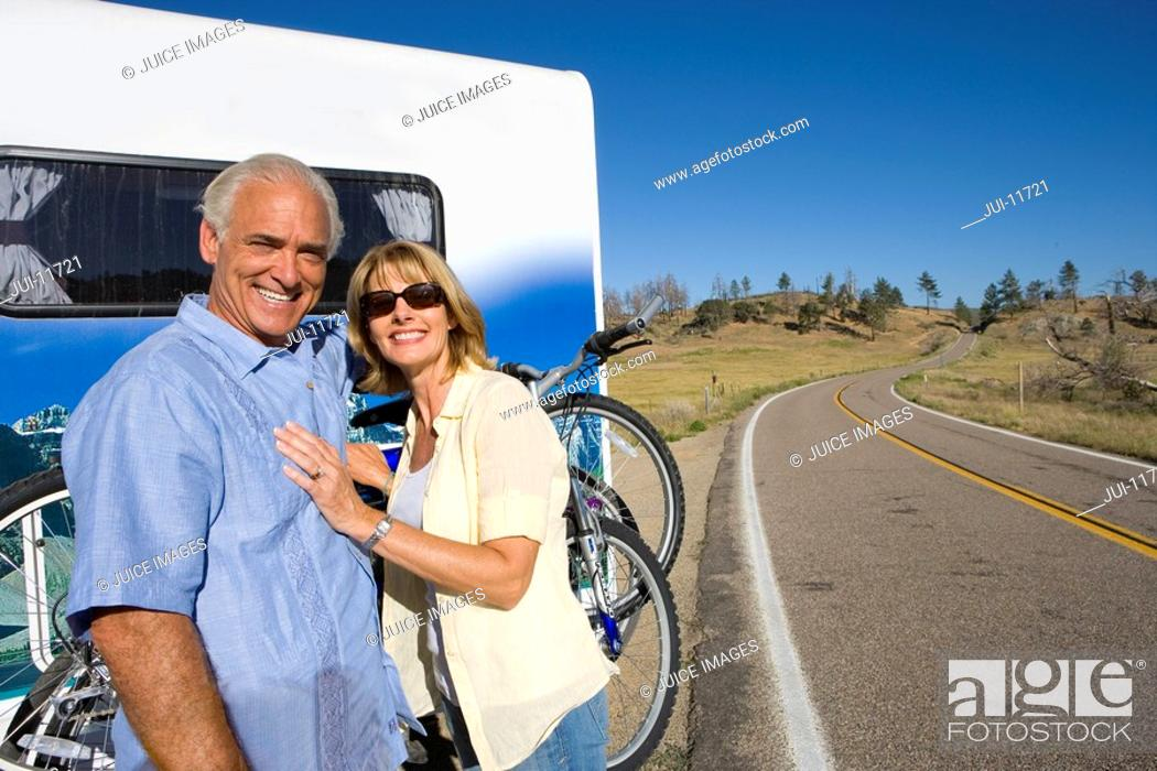 Stock Photo: Mature couple by bicycles on back of motor home, smiling, portrait.