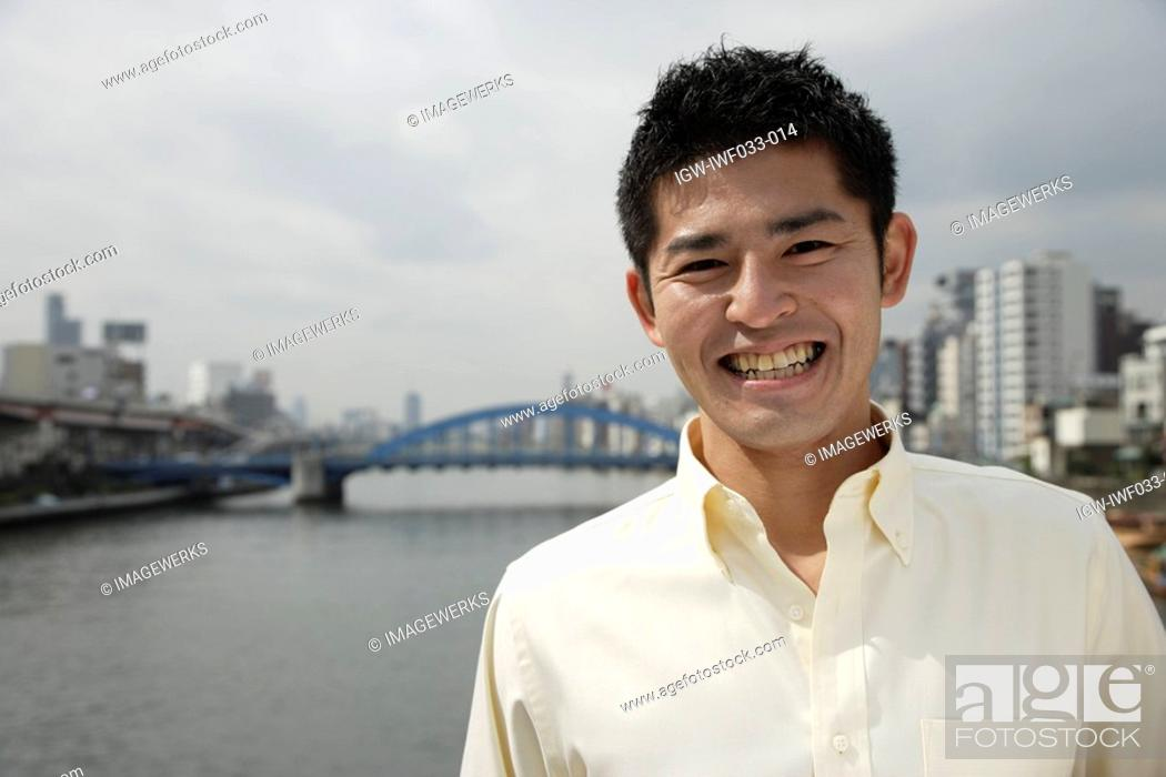 Stock Photo: A young man standing with river in background.