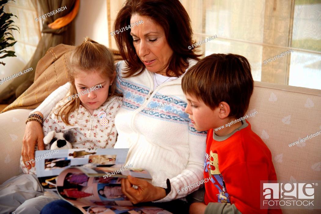 Stock Photo: Grandmother relaxing with grandchildren.
