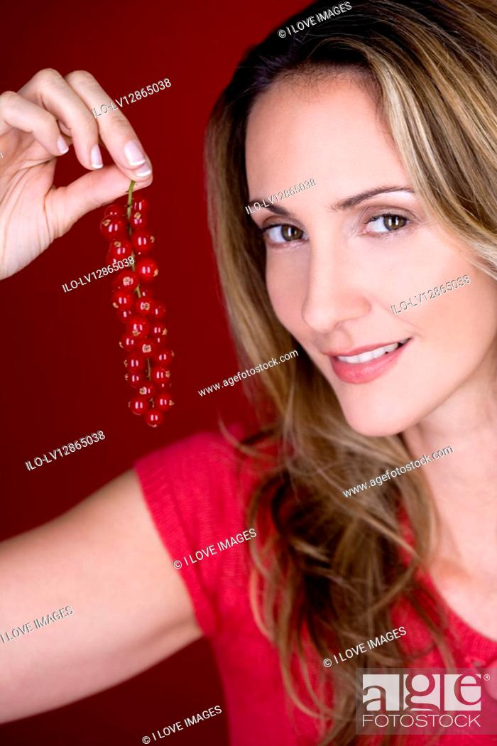 Stock Photo: A mid adult woman holding a bunch of redcurrants, smiling.