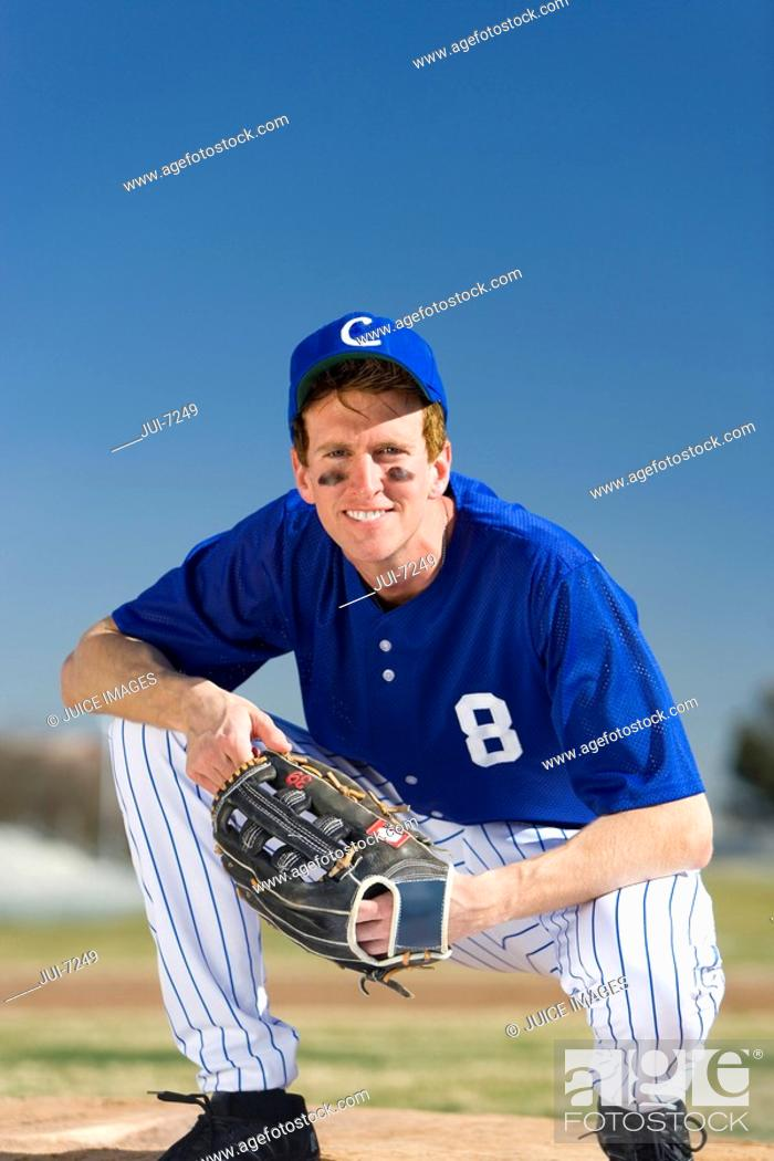 Stock Photo: Baseball player wearing blue uniform, protective glove and cap, crouching on pitch, smiling, front view, portrait.