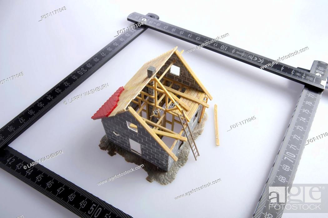 Stock Photo: A partially constructed model of a house and a folding ruler.