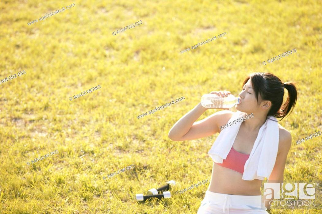 Stock Photo: A young woman drinks water as she sits amidst grassland after her workout.