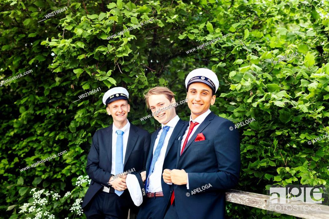 Stock Photo: Portrait of happy male graduates standing against plants.