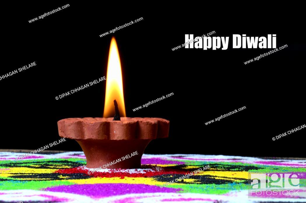 Stock Photo: Clay diya lamps lit during diwali celebration, Rangoli in background.