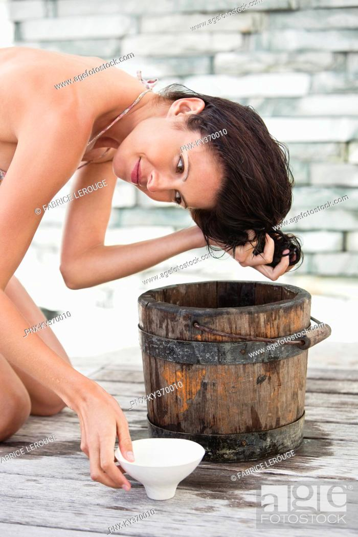 Stock Photo: Woman washing hair into a bucket.