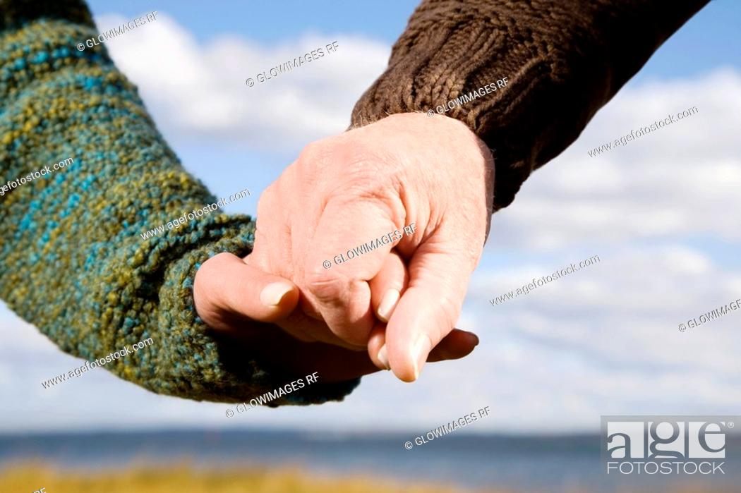 Stock Photo: Close-up of a couple holding hands of each other.