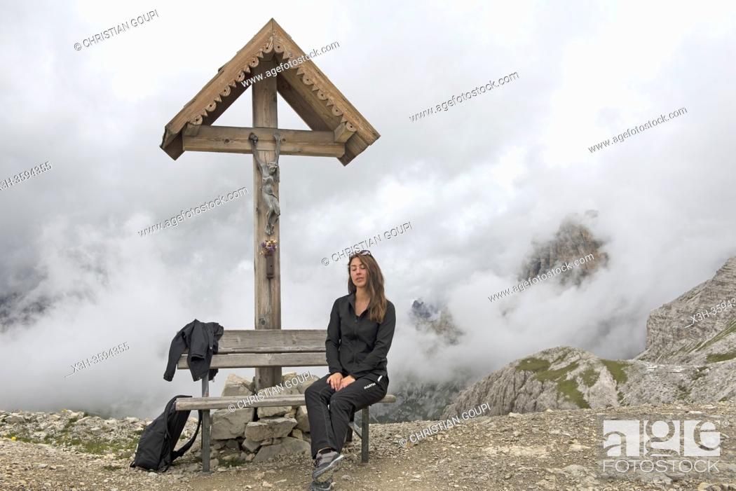 Stock Photo: jeune femme assise sur un banc sous un crucifix sur le chemin reliant les refuges Locatelli (Dreizinnenhutte) et Pian di Cengia (Bullelejochhutte).