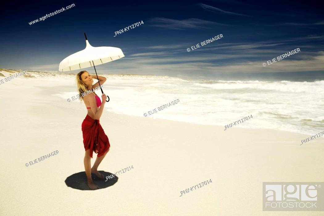 Stock Photo: Young woman in bikini and pareo with parasol on the beach.