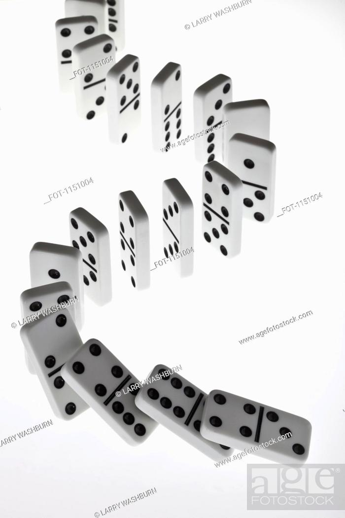 Stock Photo: Dominoes in a row, beginning to fall over in a chain reaction.