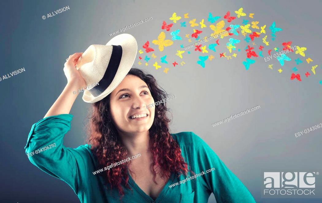 Stock Photo: Portrait of beautiful girl with hat over head and colorful butterflies flies away.