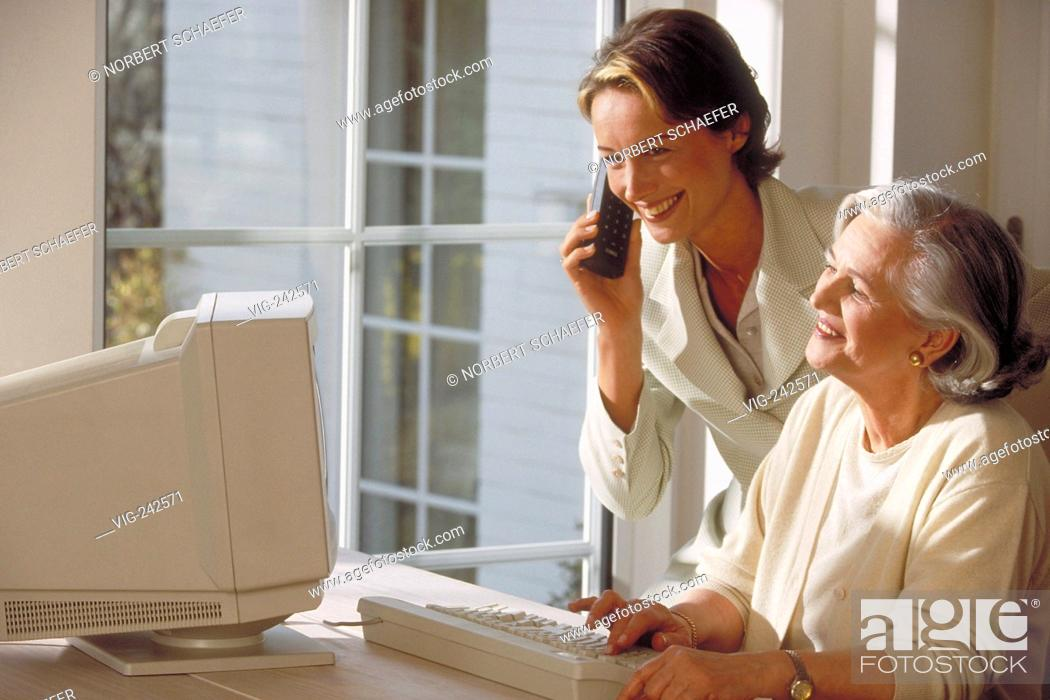 Stock Photo: indoor, ca. 30-year-old woman stands beside her mother sitting at the table near the window at the computer making a phone call  - GERMANY, 04/03/2005.