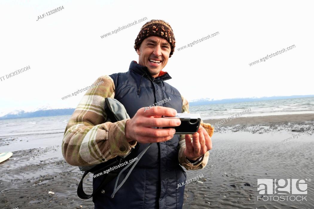 Imagen: Man on a Homer beach with a digital camera, South-central Alaska; Alaska, United States of America.