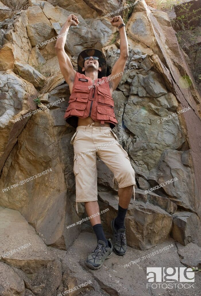 Imagen: Hiker on rocks with his arms raised.