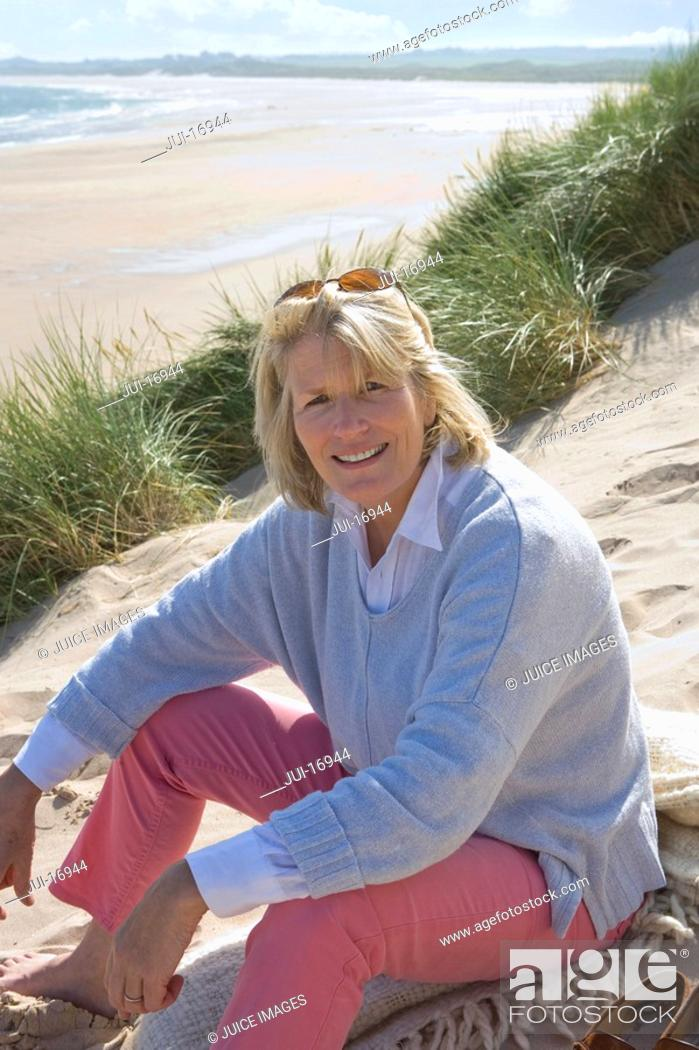 Stock Photo: Portrait of mature woman sitting on beach.
