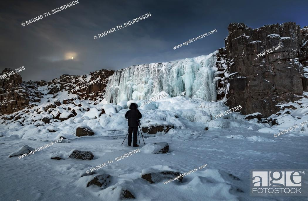 Stock Photo: Photographer taking pictures by the frozen Oxararfoss Waterfall, Thingvellir National Park, Iceland. Unesco World Heritage Site.