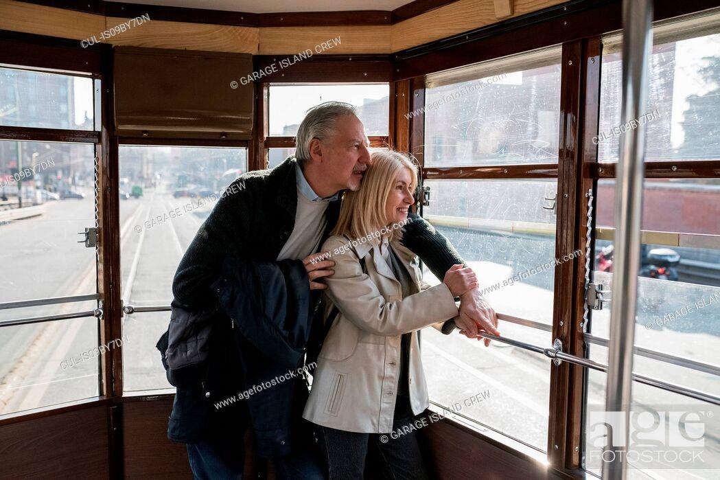 Stock Photo: Senior couple riding on tram in city.