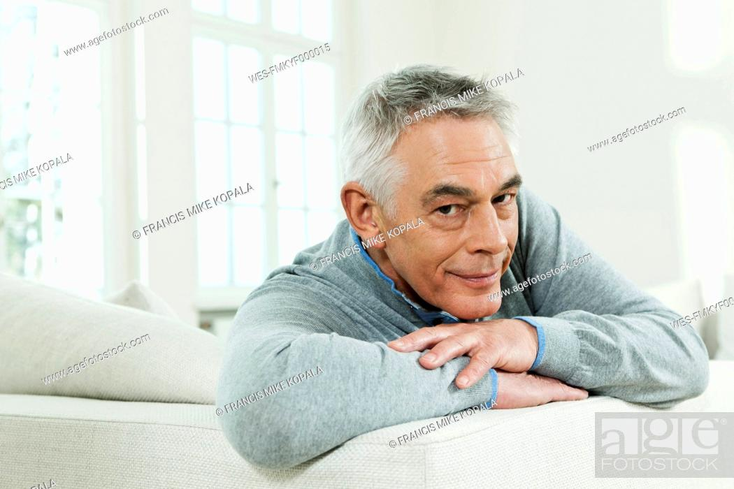 Stock Photo: Germany, Berlin, Senior man on couch, portrait.