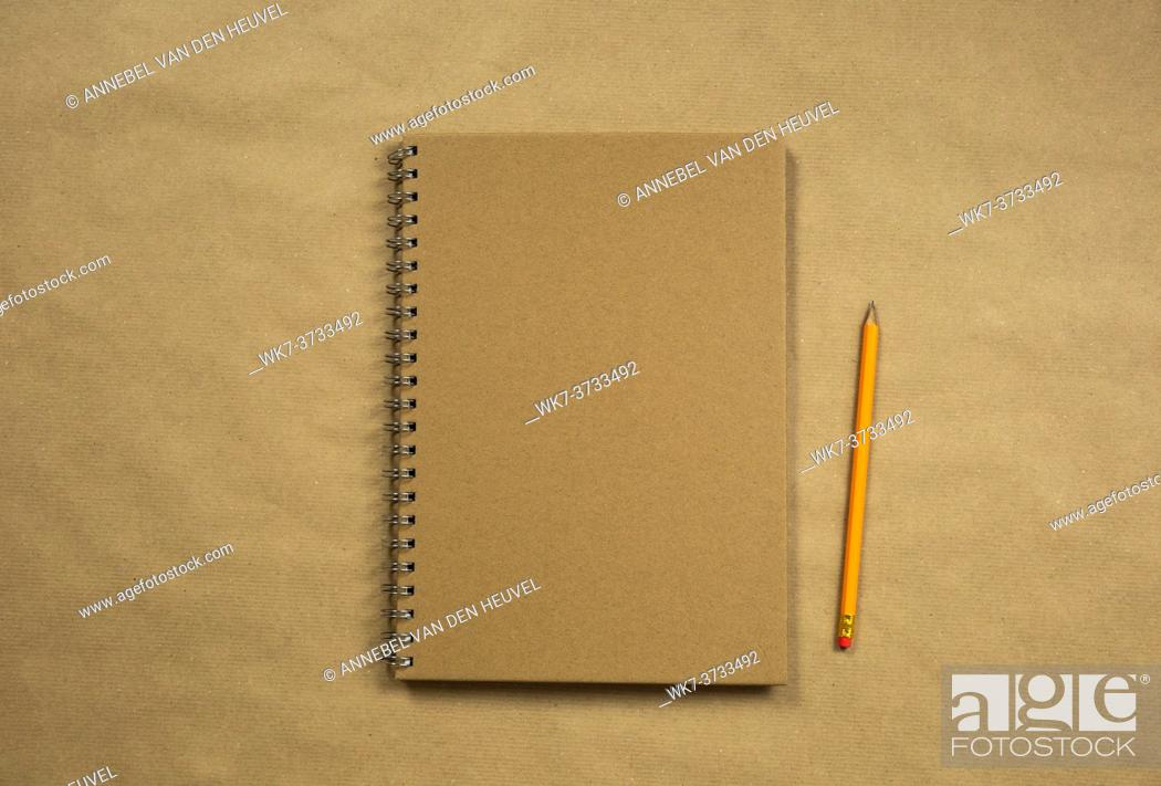 Stock Photo: Brown notebook and classic pencil on brown plain paper background texture, copy space or space for text, business or education concept top view modern retro.