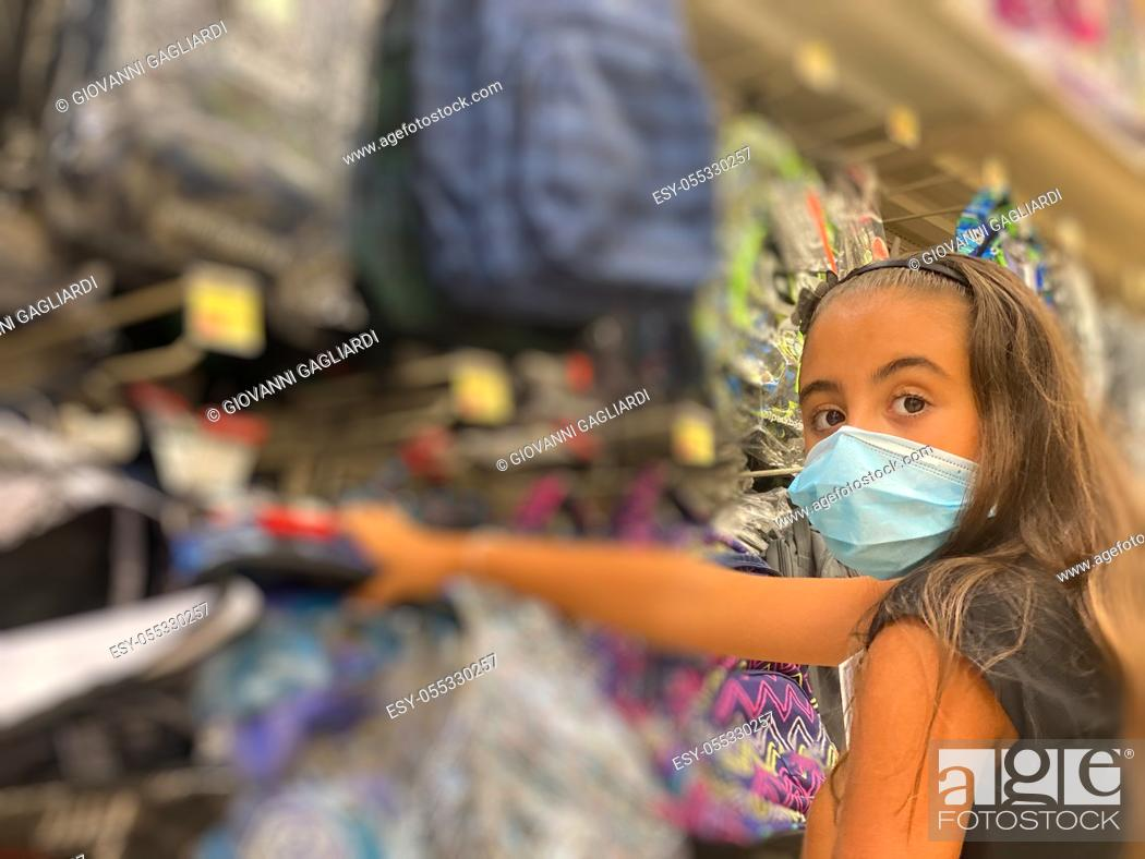 Stock Photo: Young girl wearing mask going shopping for school material.