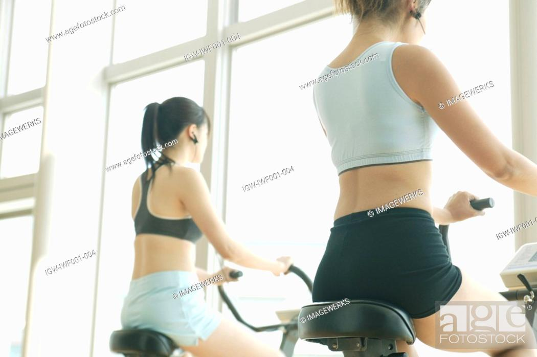 Stock Photo: Two young women perform exercise in a well equipped gym.