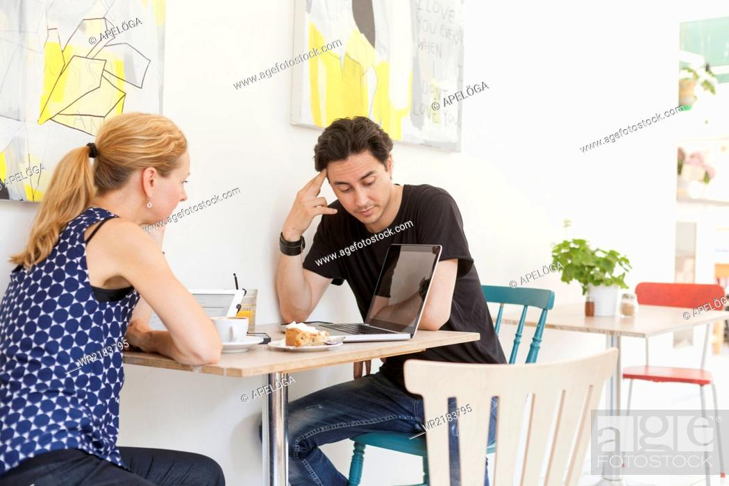 Stock Photo: Man and woman using laptop at cafe table.