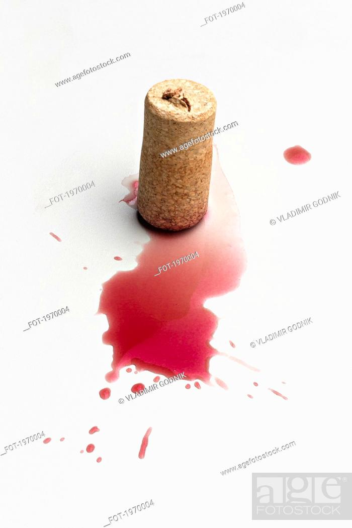 Stock Photo: Cork and red wine splatter on white background.