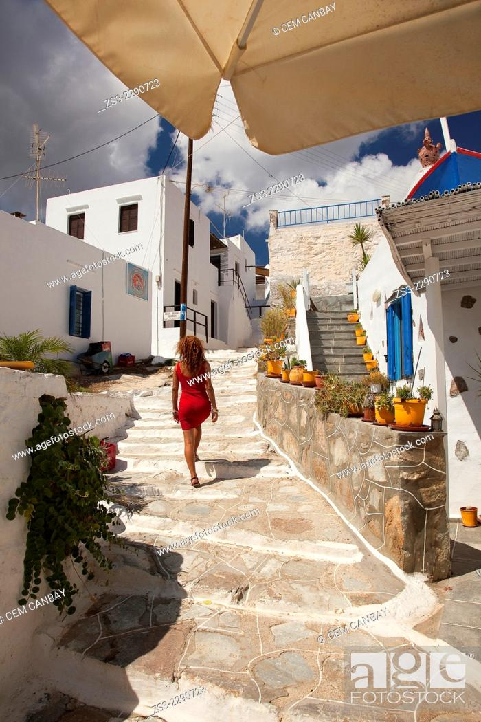 Stock Photo: Woman walking in the alley of the Faros village, Sifnos, Cyclades Islands, Greek Islands, Greece, Europe.