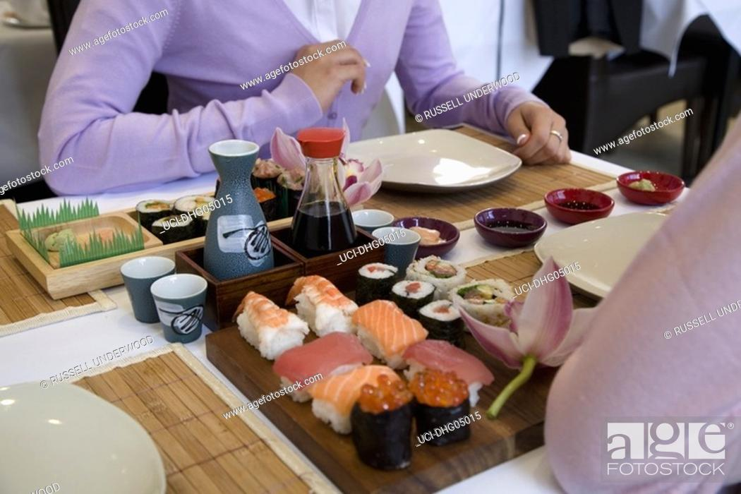 Imagen: Sushi on table between two people.