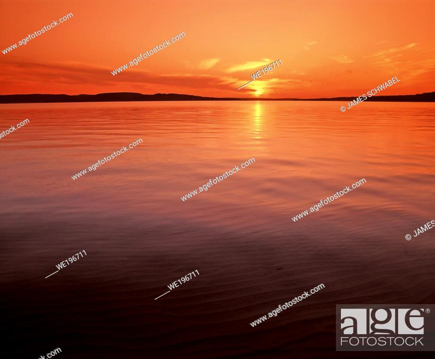 Stock Photo: Sun setting over calm smooth Lake Superior in the upper Peninsula of Michigan in the United States.
