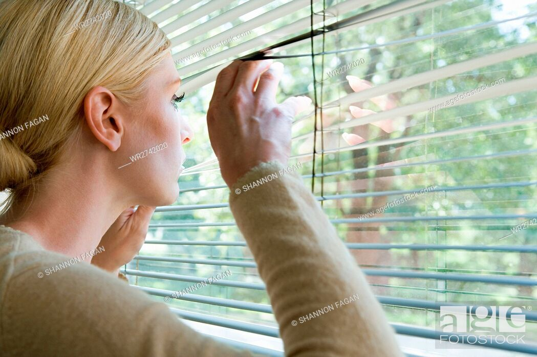 Stock Photo: Woman looking out of blinds.