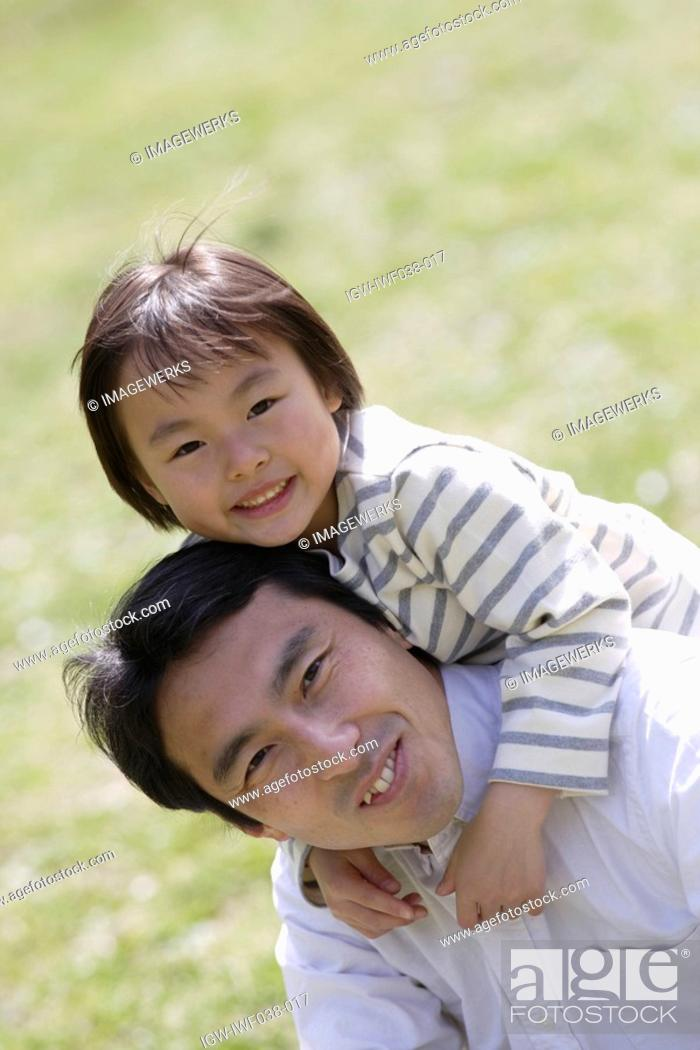 Stock Photo: Portrait of a father carrying daughter on back.
