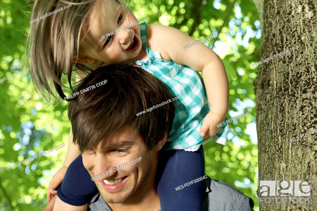 Stock Photo: Germany, Cologne, Father carrying daughter on shoulders.