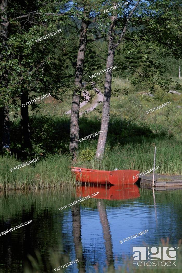 Stock Photo: A Red Boat Reflecting On A Lake In Germany.