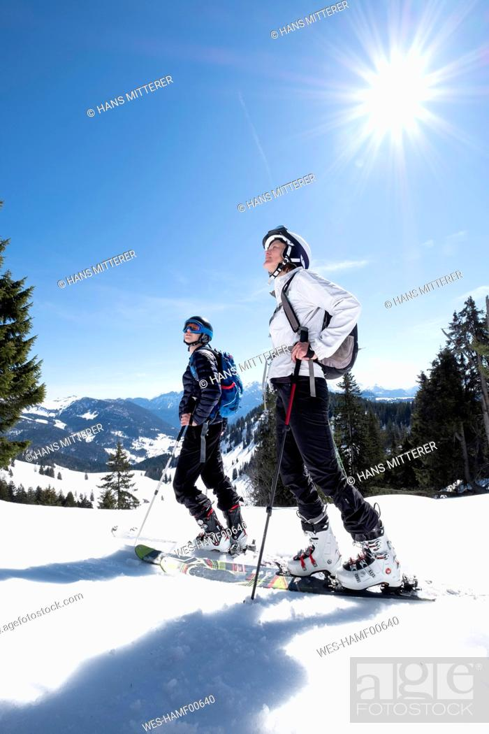 Imagen: Mother and son skiing on snow covered mountain against sky, Berchtesgaden, Bavaria, Germany.