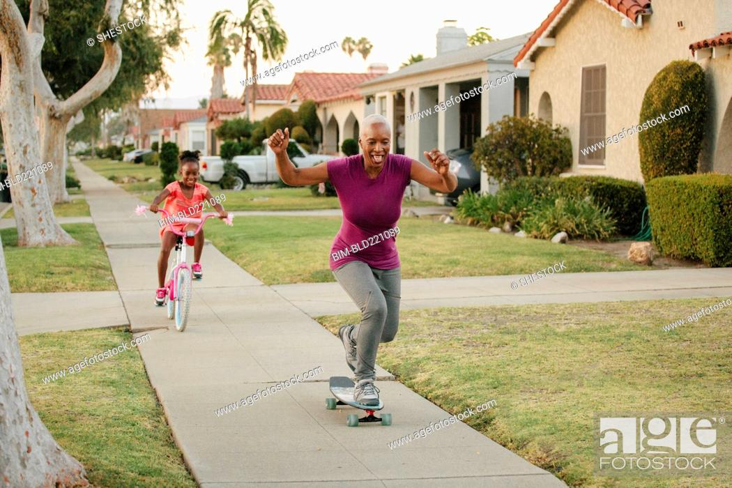 Photo de stock: Mother and daughter riding skateboard and bicycle on sidewalk.