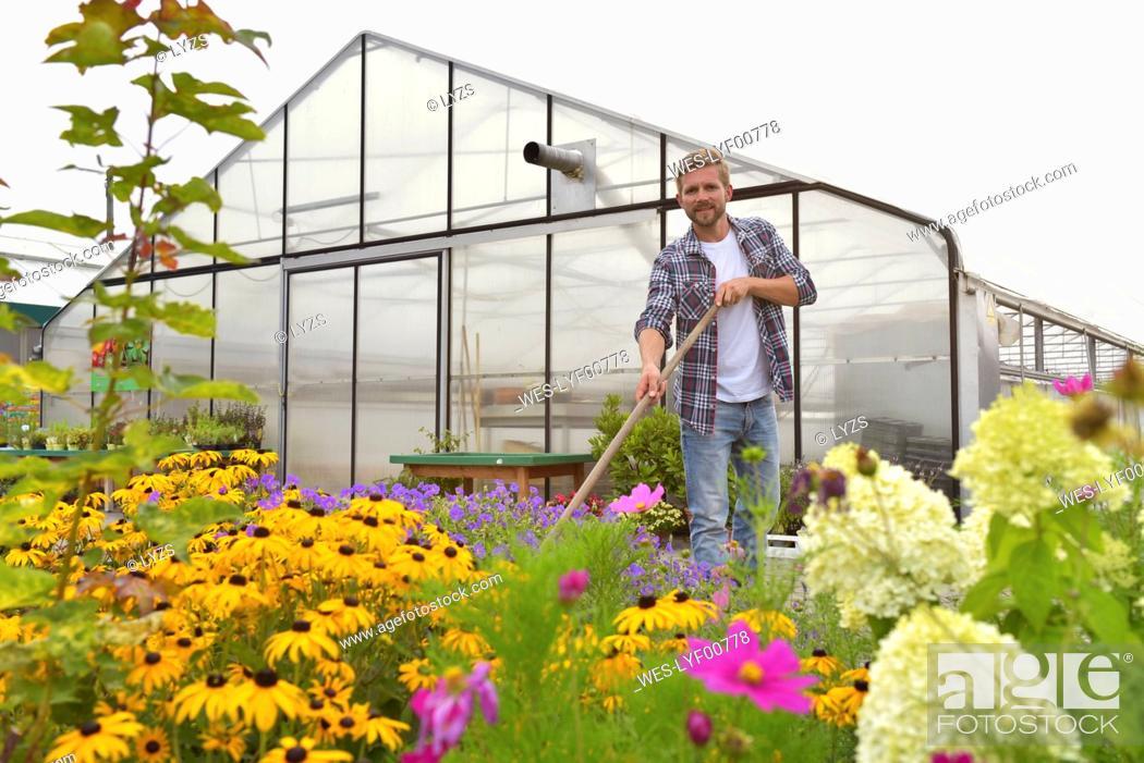 Stock Photo: Portrait of content gardener working in front of greenhouse.