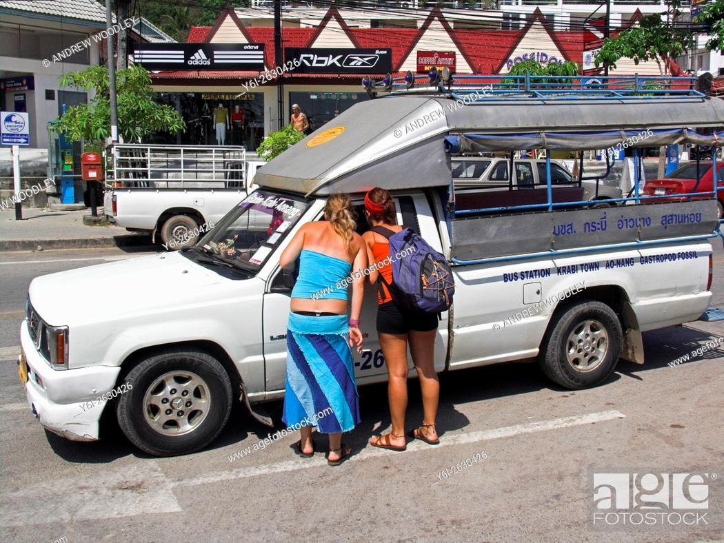 Stock Photo: Two young women visitors negotiate fare in sawngthaew shared ride taxi Ao Nang beach resort near Krabi Thailand.