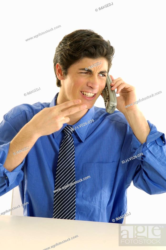 Stock Photo: Businessman talking on a cordless phone and making a gun sign.