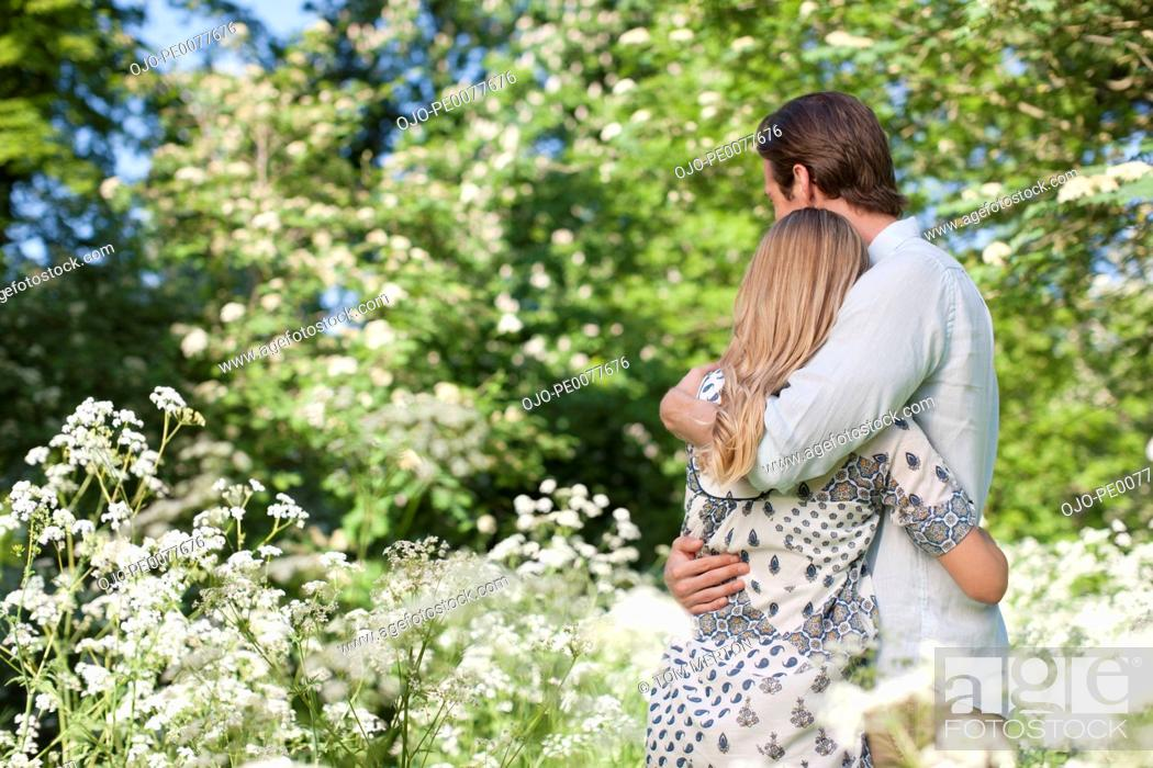 Stock Photo: Couple hugging in field of flowers.