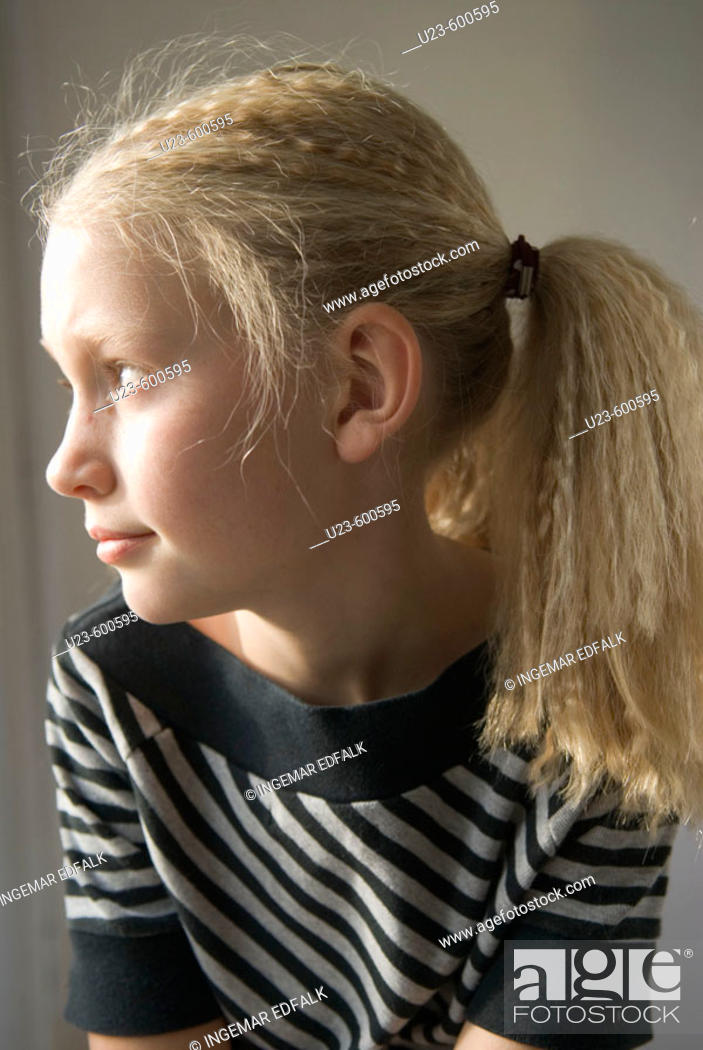 Stock Photo: Young girl by the window.
