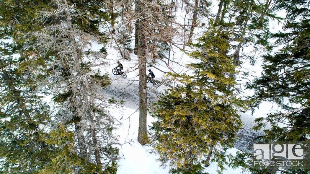 Imagen: Aerial view of two mountain bikers riding on road covered by snow in forest outdoors in winter.