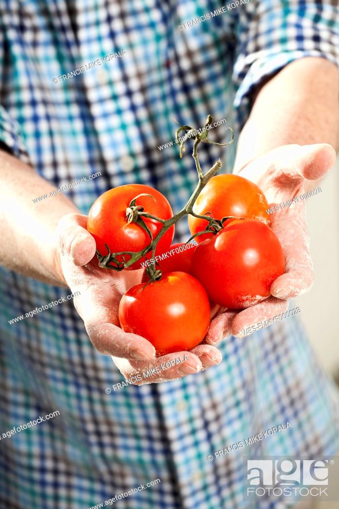 Stock Photo: Germany, Berlin, Senior man holding tomatoes.