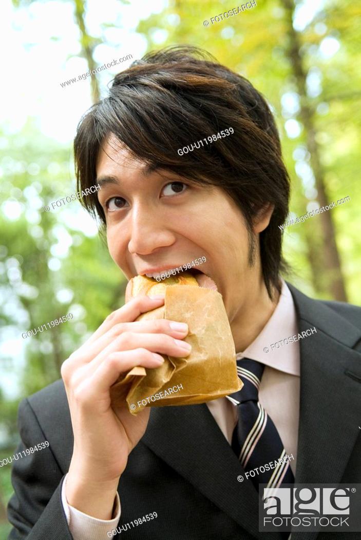 Stock Photo: The Businessman Who Eats Sandwich.